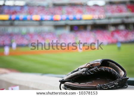 Baseball glove on the wall with a major league stadium in the background - stock photo