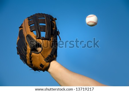 Baseball in air about to be caught by glove with blue sky background.