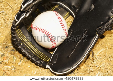 Baseball in glove over dirt, horizontal image - stock photo