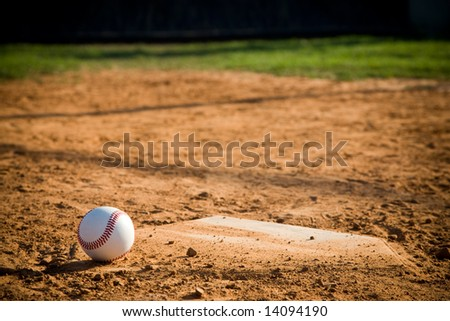 Baseball in lower left corner sitting on a dirty home plate. - stock photo