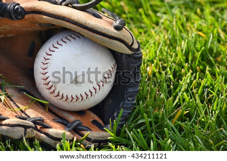 baseball in worn leather sports glove on grass - stock photo