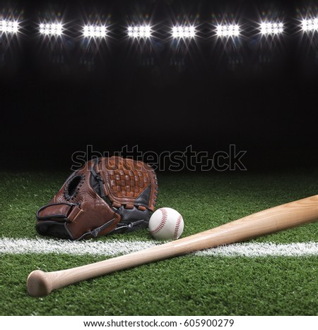 Baseball mitt ball and bat at night under stadium lights on grass field with white stripe
