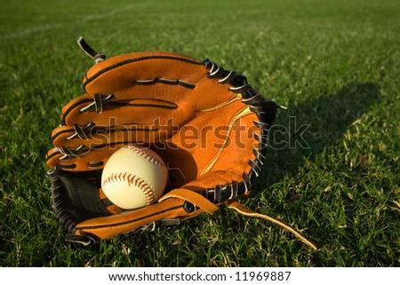 Baseball mitt with baseball on a lush, green field - stock photo