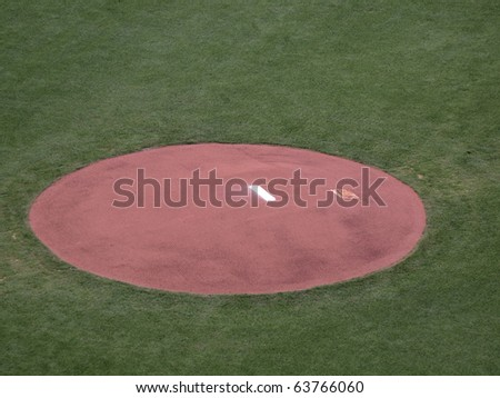 Baseball mound sits empty in pregame perfection before players begin destroying the surface with their cleats. - stock photo