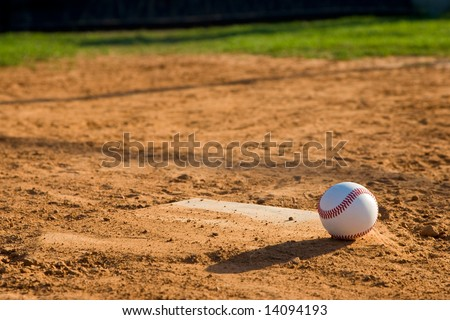 Baseball on lower right corner sitting on a dirty home plate. - stock photo