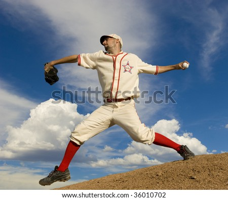 Baseball pitcher on pitcher's mound at full stretch about to release the ball. Set against a bright blue sky. Horiztonally framed shot. - stock photo