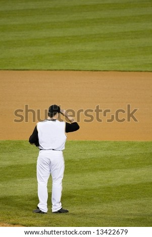 Baseball pitcher standing in infield - stock photo