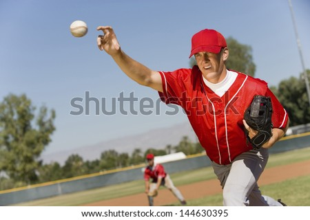 Baseball pitcher throwing a ball - stock photo