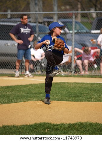 Baseball pitcher throwing the ball on the mound - stock photo