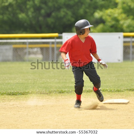 Baseball player at second base.   The young boy is wearing a red and black uniform.