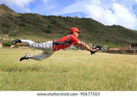 Baseball player dives for the ball in the outfield - stock photo