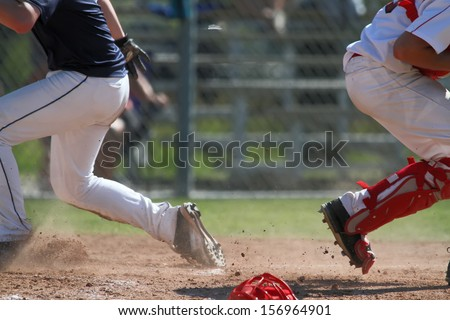 Baseball player getting to home plate with unknown results - stock photo