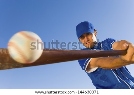 Baseball player hitting the ball with a bat against clear blue sky - stock photo