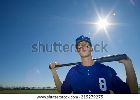 Baseball player, in blue uniform and cap, standing on pitch with bat behind head, front view, portrait (lens flare) - stock photo