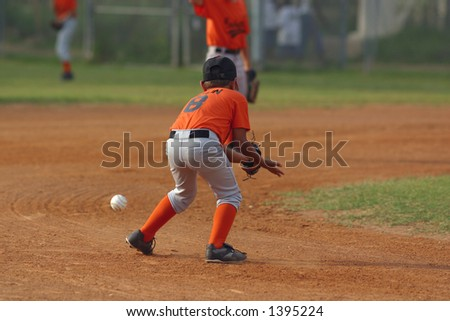 Baseball player lining up to catch a ball in play. - stock photo