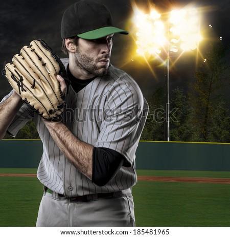 Baseball Player on a Green Uniform on baseball Stadium. - stock photo