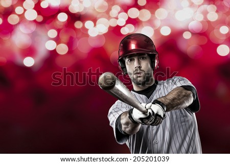 Baseball Player on a Red Uniform on red lights background.