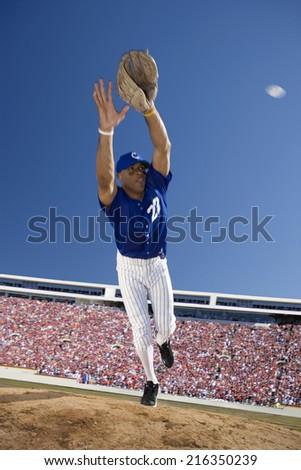 Baseball player reaching to catch baseball - stock photo