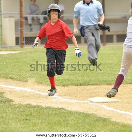 Baseball player running towards first base.  The umpire is in the background.  The young boy is wearing a red and black uniform. - stock photo