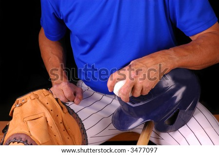 Baseball player sitting on bench with helmet, bat and ball , with black background - stock photo