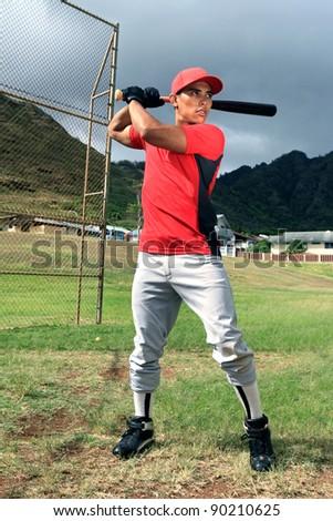 Baseball player stands at bat - stock photo