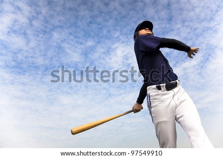 baseball player taking a swing with cloud background - stock photo