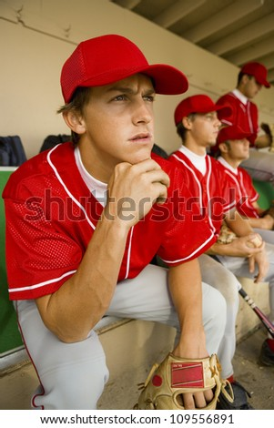 Baseball player watching the game intensely while sitting in dugout with other players - stock photo