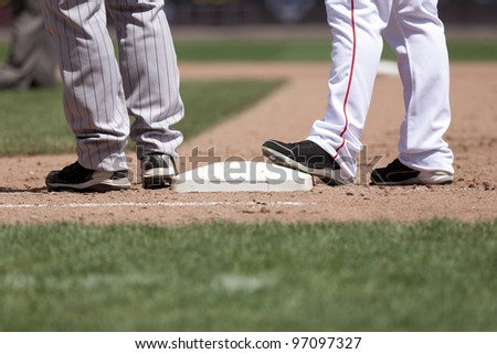 baseball players at 1st base on a sunny day - stock photo