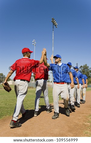 Baseball players giving high-five to each other after match - stock photo
