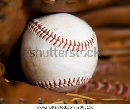Baseball sitting inside of a baseball glove - stock photo