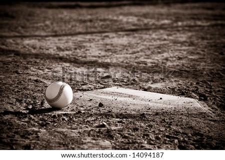 Baseball Sitting on a dirty baseball home plate with vintage sepia look and vignette - stock photo