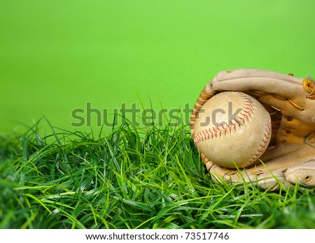 Baseball softball, glove in the grass with green background and copy space