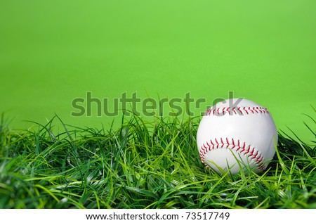 Baseball softball in the grass with green background and copy space - stock photo