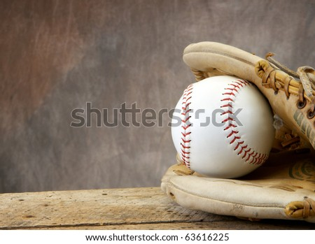 Baseball/softball with mit on old wood table and tan aged background with copy space - stock photo
