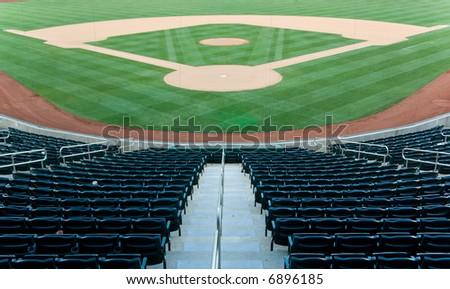 Baseball stadium with seating and a baseball diamond with green grass - stock photo