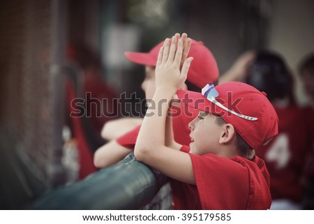 Baseball team in the dugout, cheering for their team, shallow focus, focus on hat. - stock photo