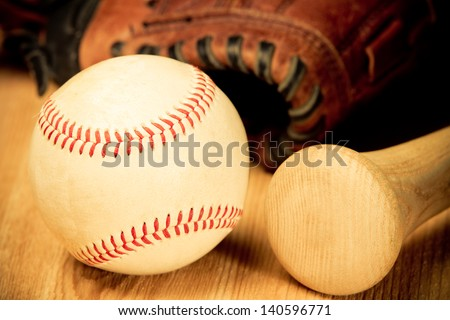 Baseball - This is a close up shot of an old baseball and wooden bad on a wood background with an old glove in the background. Shot in a warm retro color tone. - stock photo