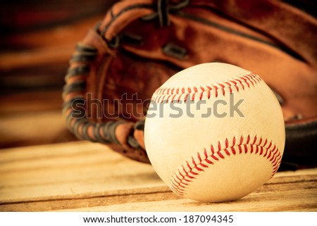 Baseball - This is a shot of an old worn baseball sitting in front of an old glove. Shot in a warm retro color tone with a shallow depth of field. - stock photo