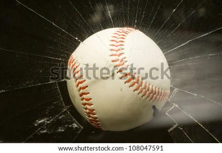 Baseball through broken window. - stock photo