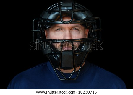 Baseball Umpire.  Head shot of handsome middle-aged man wearing an umpire's mask.  Isolated against black background. - stock photo