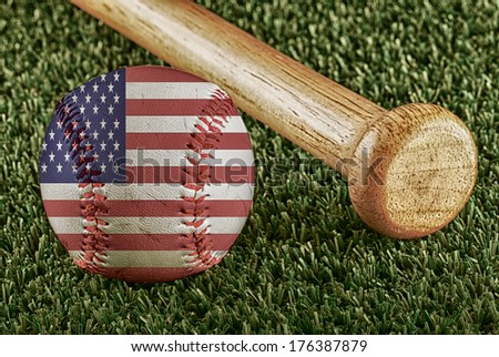 Baseball with USA flag and bat over a background of green grass - stock photo