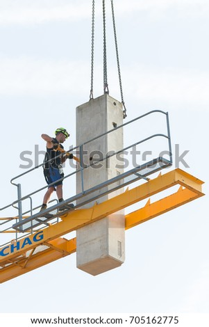 Basel, Switzerland, August 29, 2017 - Worker in the process of removing a tower crane disassembling it bit by bit. The ballast support bar is removed from the counterweight during the removal.