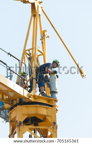 Basel, Switzerland, August 29, 2017 - Workers in the process of removing a tower crane disassembling it bit by bit. The motor for turntable movement is being prepared for manual operation.