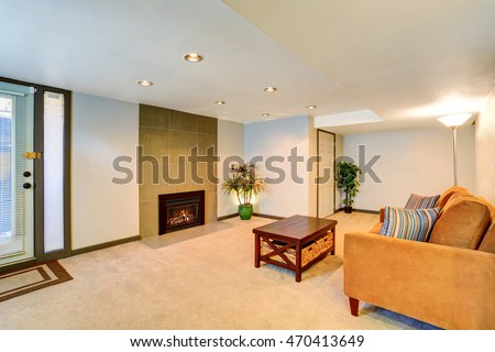 Basement living room interior with fireplace and brown couch. Northwest, USA