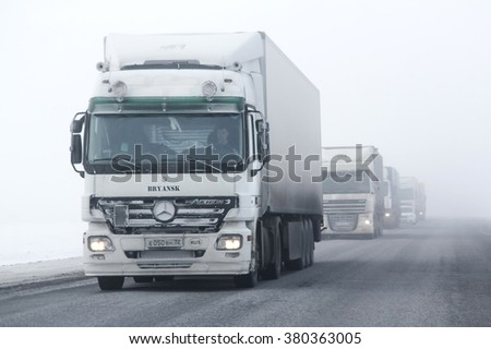 BASHKORTOSTAN, RUSSIA - FEBRUARY 7, 2016: Semi-trailer truck Mercedes-Benz Actros at the interurban freeway during a heavy fog. - stock photo