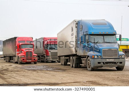 BASHKORTOSTAN, RUSSIA - MARCH 22, 2015: Semi-trailer trucks at the dusty parking near the interurban freeway. - stock photo