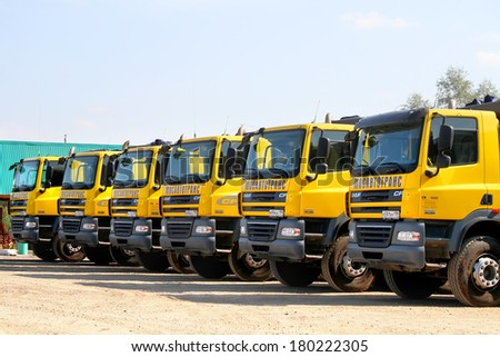 BASHKORTOSTAN, RUSSIA - SEPTEMBER 6, 2009: Line of new yellow DAF CF dump trucks at the parking.