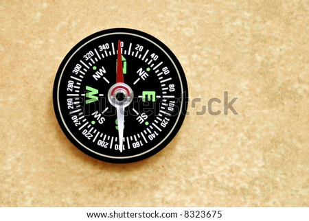 Basic compass lying on the sand - stock photo