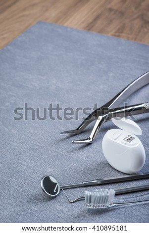 Basic dental tools, floss and brush on grey table
