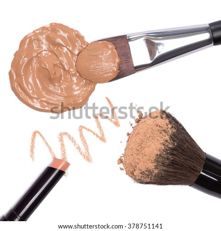 Basic makeup products to create beautiful skin tone and complexion. Concealer pencil, foundation, loose cosmetic powder with brushes. Close-up on white background